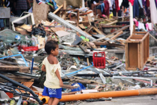 Photo 2 A child walks in the rubble after supertyphoon Yolanda ravaged central Philippines. Photo by April SumayloSave the Children.