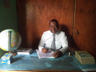 Principal Jeanty behind his desk