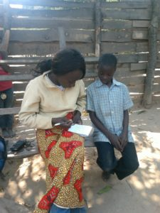 Noble being interviewed and learning about Sponsorship from Save the Children staff
