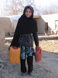 Nazdana collecting water outside her home
