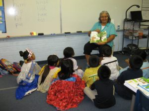 Gloria reads a story to children during our literacy programs.