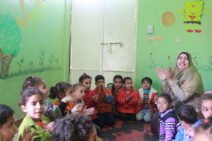 Rania and the other kids clap along to a group activity led by their teacher, Mirvat