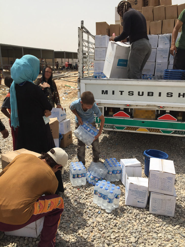 A new IDP family receiving their RRM kit:  1 Hygiene Kit, 1 dignity kit, 1 food kit and 2 containers of water.