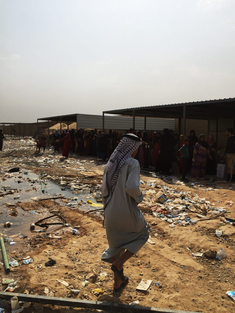 A man walks through the dirty screening center to line up for distribution. Save the Children are currently doing waste management to clean the screening center of rubbish and make it more livable for IDPs stuck in the area.