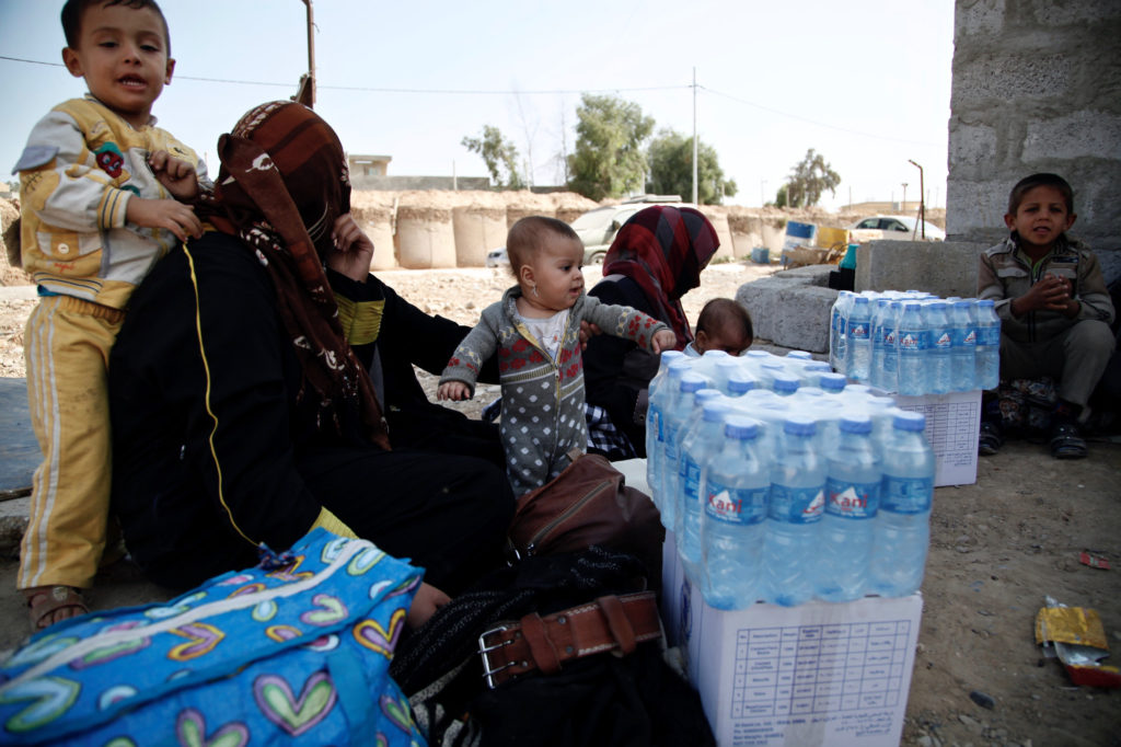 A group of mothers sit with their children at Dibis checkpoint near the Iraqi city of Kirkuk.