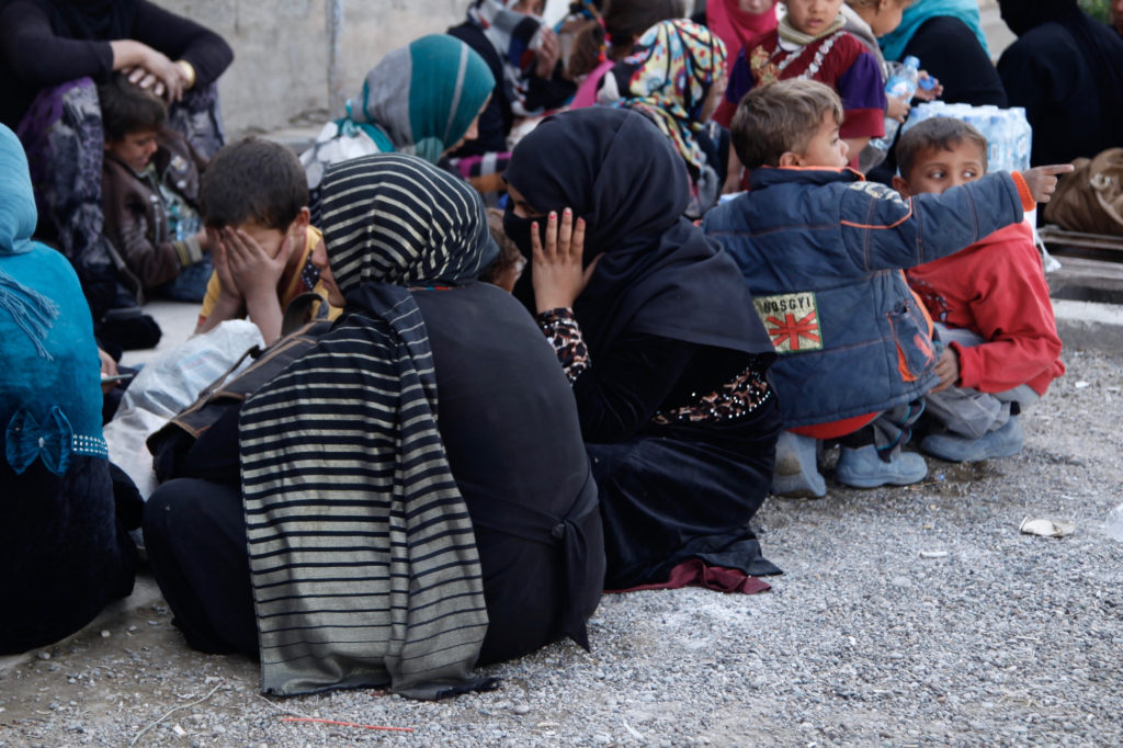 Kirkuk, Iraq. 16th October, 2016. A group of mothers sit with their children at Dibis checkpoint near the Iraqi city of Kirkuk.