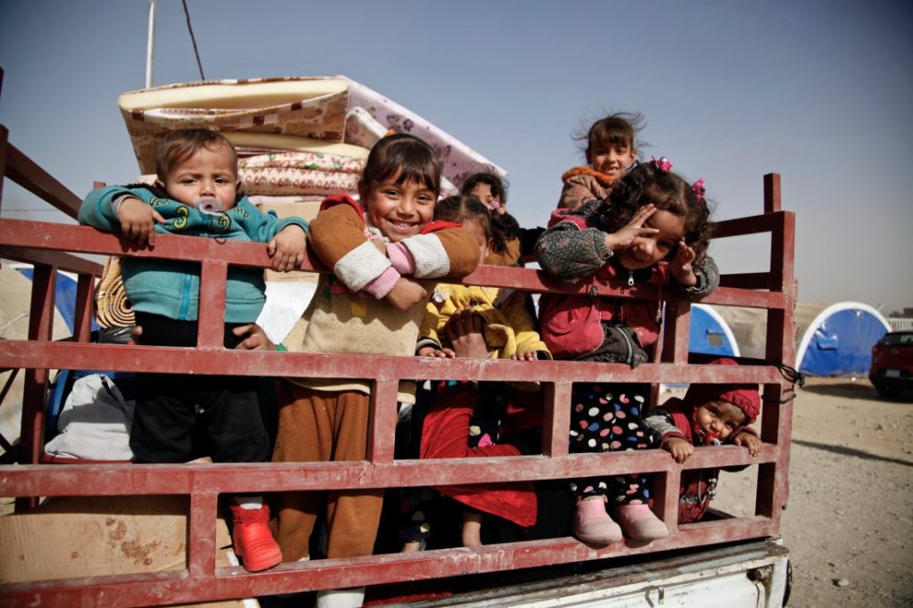 November 20, 2016. Qayyarah, Iraq. Children stand in the back of a truck as their family prepares to return home from Qayyarah Jad'ah camp.