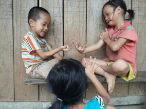 Yen playing with her siblings outside their home.