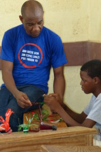 A child participating in one of our summer camp activities, making art from recyclables.