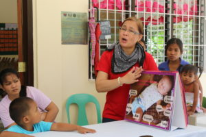 Florenda sharing information about breastfeeding and nutrition with new mothers.