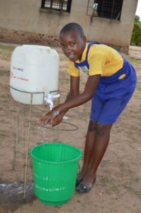 Robinah washing her hands using a handwashing facility provided through funds from sponsors.