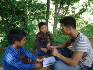 Tribhuvan following up with Aashik (middle) and his friend about how returning to classes is going.