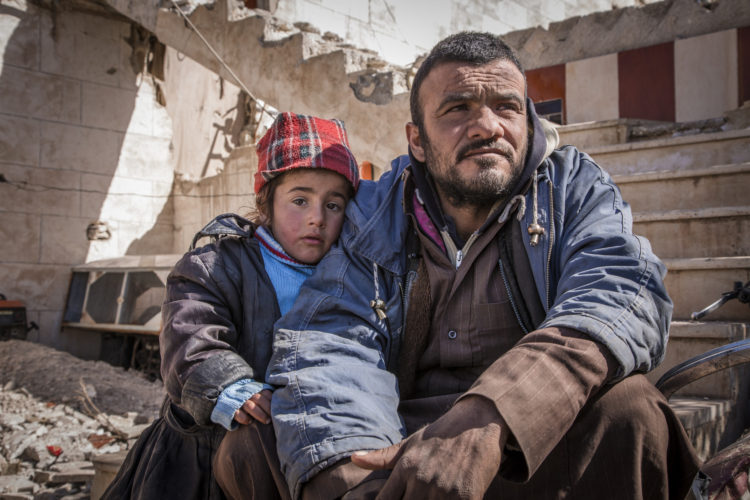 Firas* sits with his daughter, Layla*, five, at an abandoned petrol station where he and his family now live. .The petrol station, badly damaged by war, is now the home of five families who have returned to Tel Abiad district, Raqqa Governorate, Syria, after fleeing from ISIS two years earlier only to find their homes destroyed.