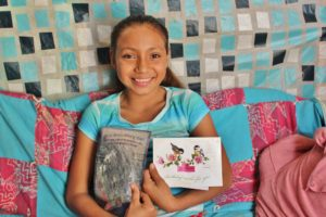 Berta proudly shows her two favorite letters from her sponsor.