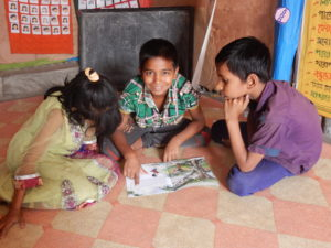 Sajib reading a storybook with friends Firoza and Rabibul at the center.