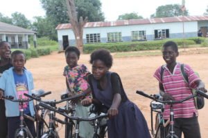 Giveness smiling with her friends outside of their sponsorship supported school.