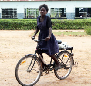 Giveness with her bicycle, which cuts her 3-hour ride to school to just 1 hour!
