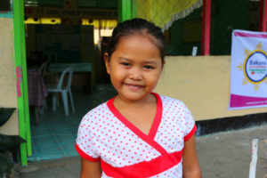 Maria smiling in front of her classroom.