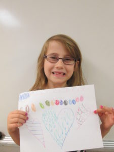 Sarabeth proudly shows her drawing.