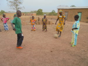 Oumar playing with his friends in the school yard, happy to be attending classes again.