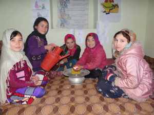 Amina and her fellow child-focused health education group members practice safe handwashing.