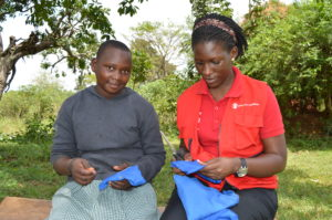Gloria and Agnes, Senior Officer of our adolescent development programs, making reusable pads.
