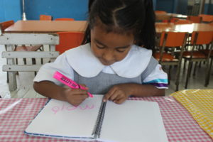 Melany shows how she's learned to write her name.