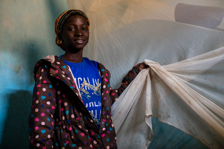 "12-year-old Gniré holds onto her mosquito net which hangs above her bed inside of her bedroom on Thursday, January 25, 2018 in Sikasso, Mali. In 2017, Gniré was diagnosed with malaria, twice and then treated. Thanks to Save the children, Gniré has been provided with medication twice a year along with a mosquito net which she sleeps under every night. ""I am thankful for Save the Children in my community because it means that they care about my health."""