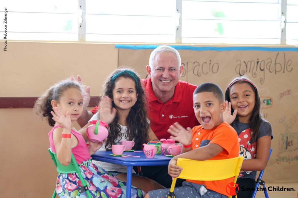 Carlos Carrazana, Chief Operating Officer of Save the Children, visits with children playing in a Community Based Children's Activity (CBCA) site in Orocovis, Puerto Rico, in the fall of 2017. The CBCA was set-up by the community in response to Hurricane Maria. The CBCA provides a space for children to play and learn while they wait for schools to reopen.