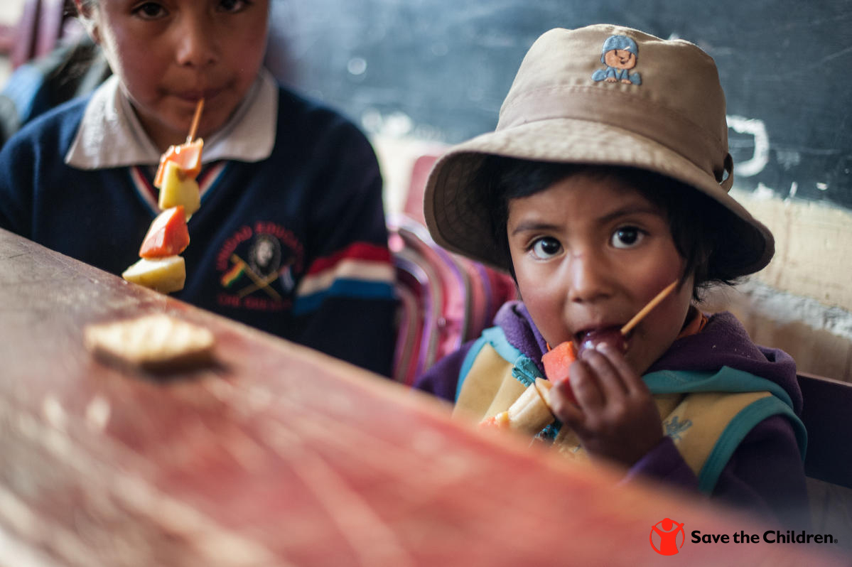 At a Save the Children-supported school in Bolivia, young children enjoy healthy snacks.