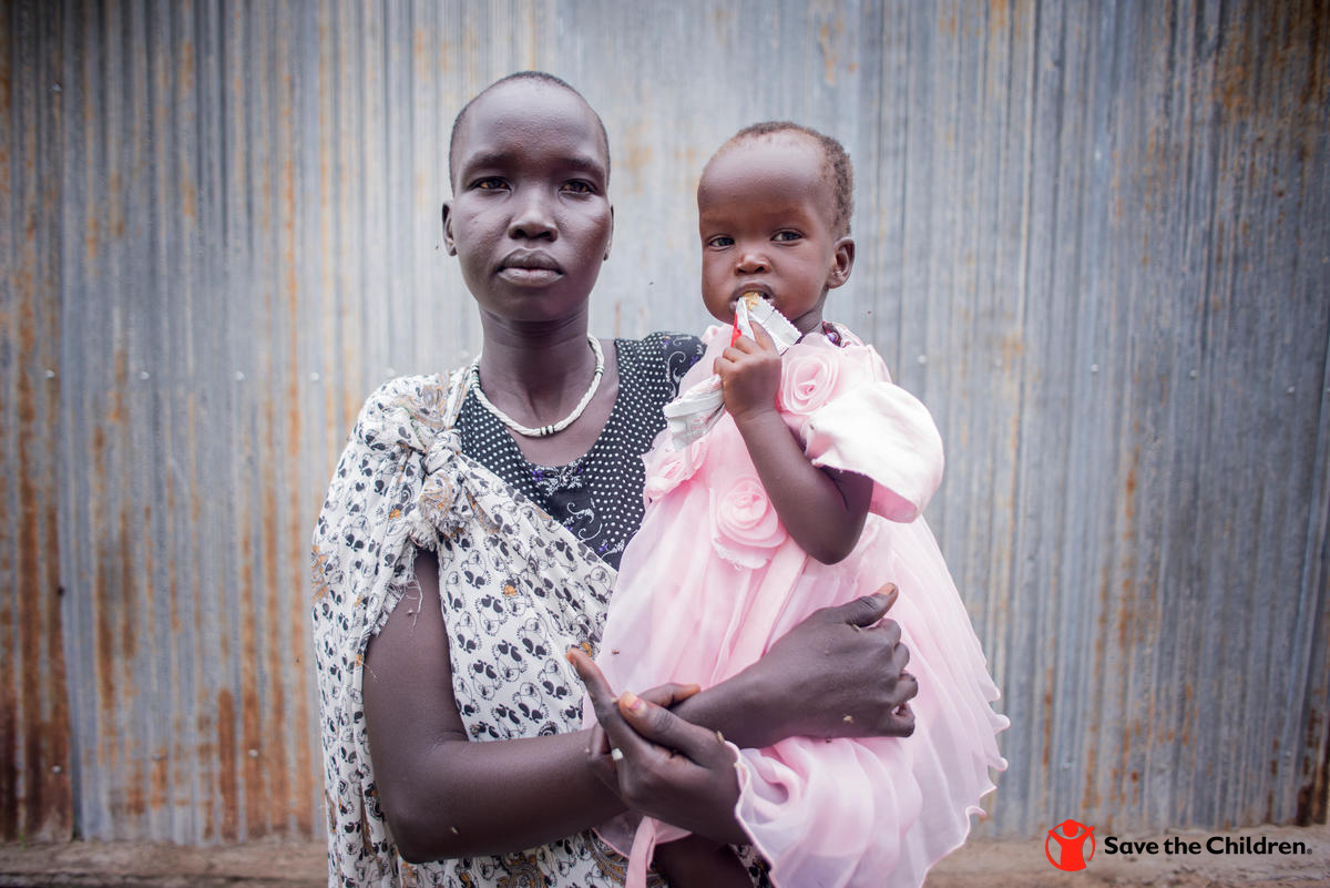 Rebecca, 25, holds her daughter Rachael*, 11 months while she eats high nutrient peanut paste after being treated for severe acute malnutrition at a Save the Children stabilization center in South Sudan.