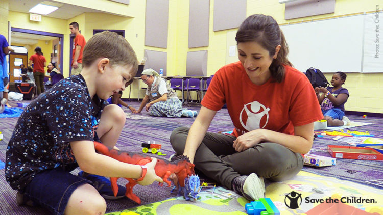 A Save the Children staffer plays with a child in a safe play space, set up to help children cope with the devastating effects of Hurricane Michael.